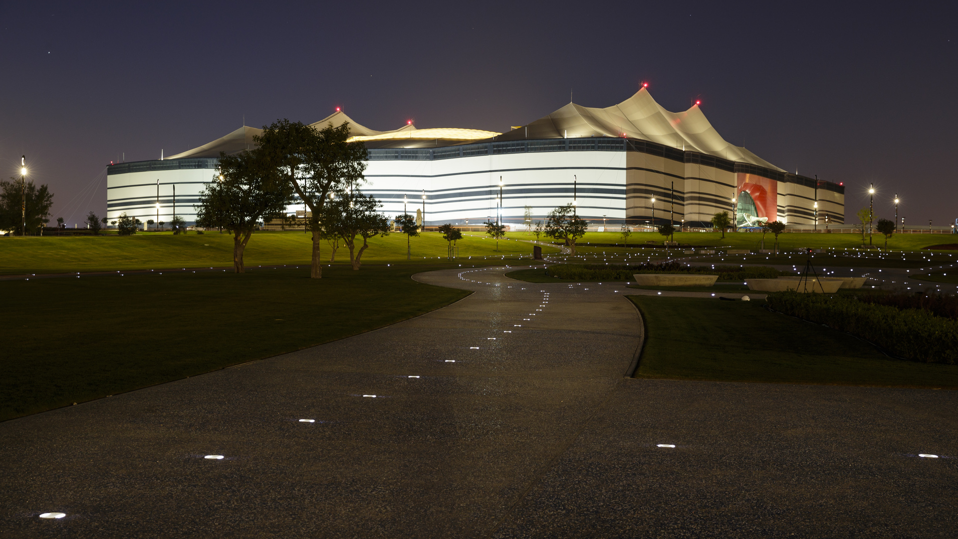 A view of Al Bayt Stadium, lit up at night.