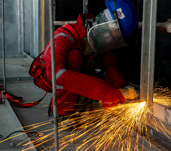 Worker wearing personal protective equipment while cutting metal