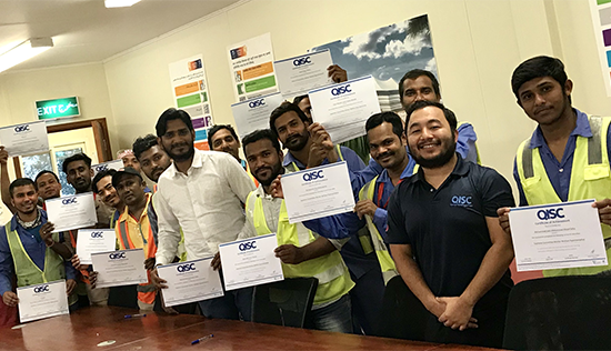 Workers holding up training certificates