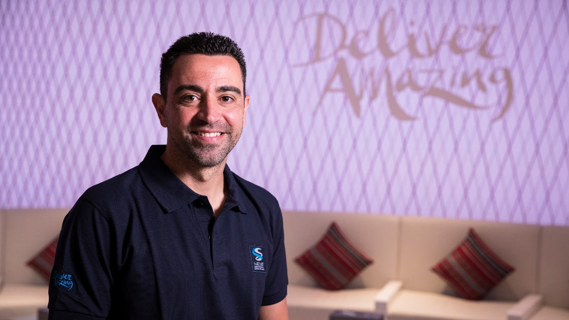 Xavi in front of Deliver Amazing backdrop
