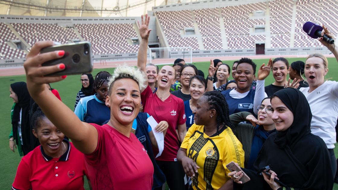 Lianne Sanderson taking a selfie with a group of young women from Generation Amazing at Khalifa Stadium in Doha.