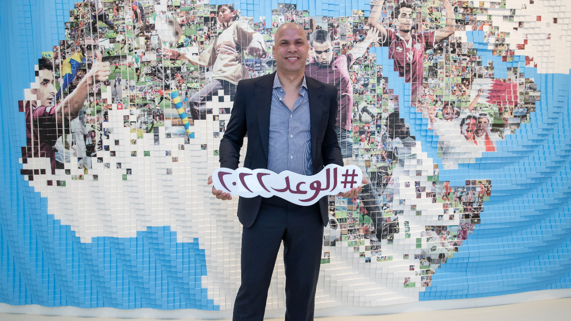 """Wael Gomaa holding up an Arabic language sign that says """"See You in 2022!"""""""