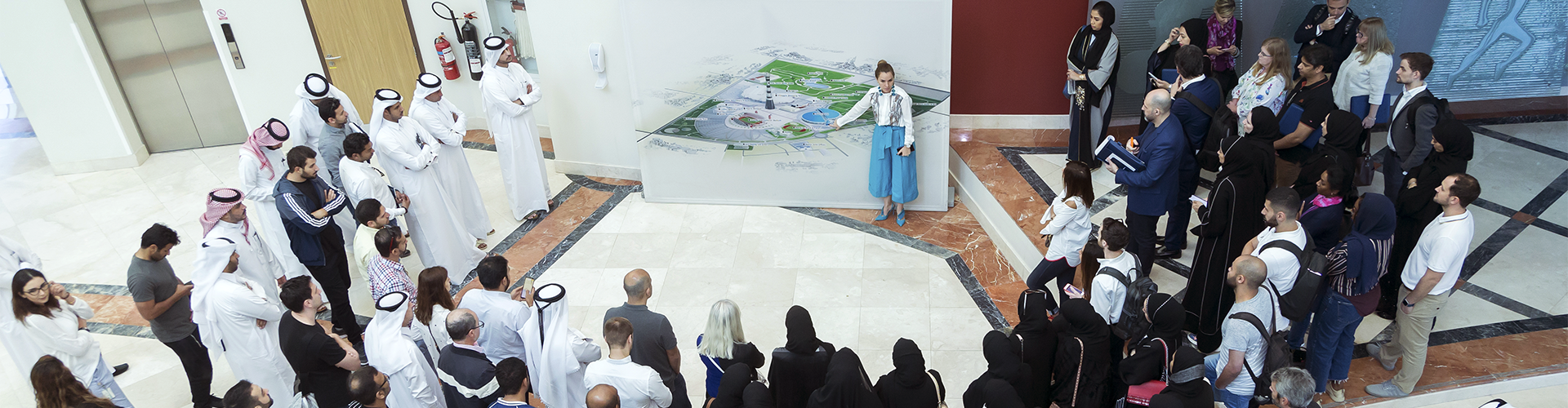 A group of people watching a presenter at an exhibition