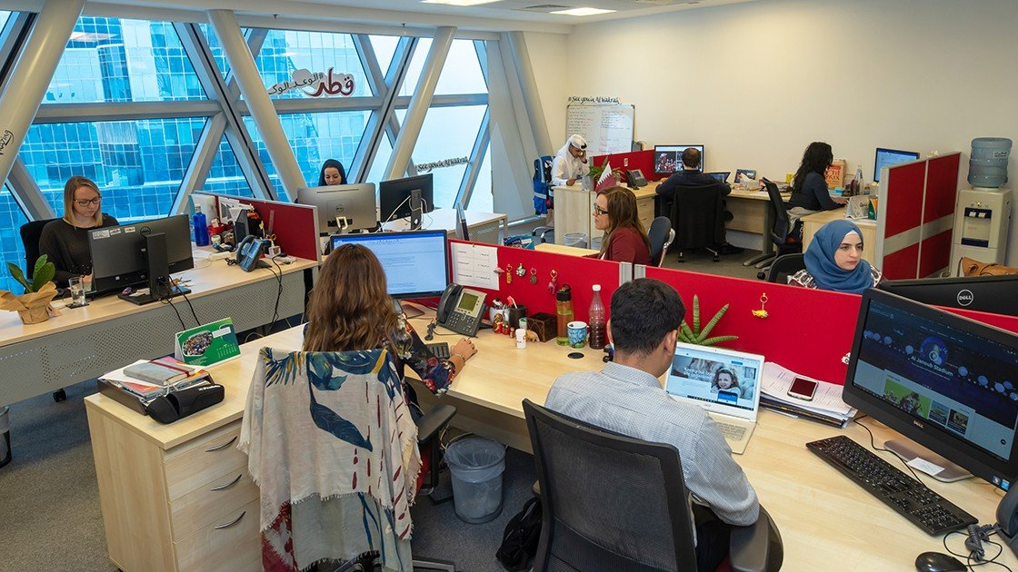 Supreme Committee for Delivery & Legacy employees working at their desks in an open-plan office.