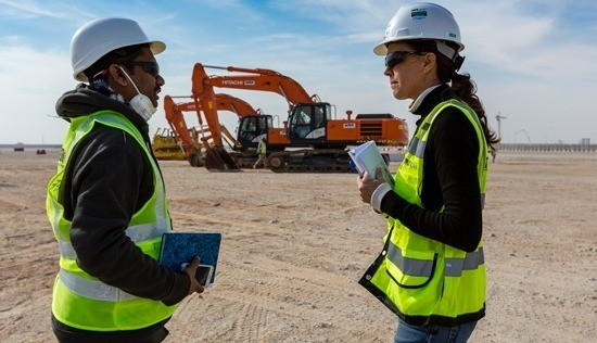 Two people talking on a construction site