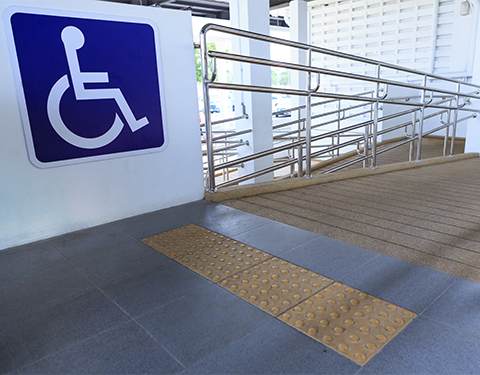 A wheelchair sign and accessibility ramp